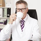 male-doctor-drinking-cup-tea-coffee-middle-aged-as-sits-his-desk-his-office-looking-down-his-desk-43173283[1]